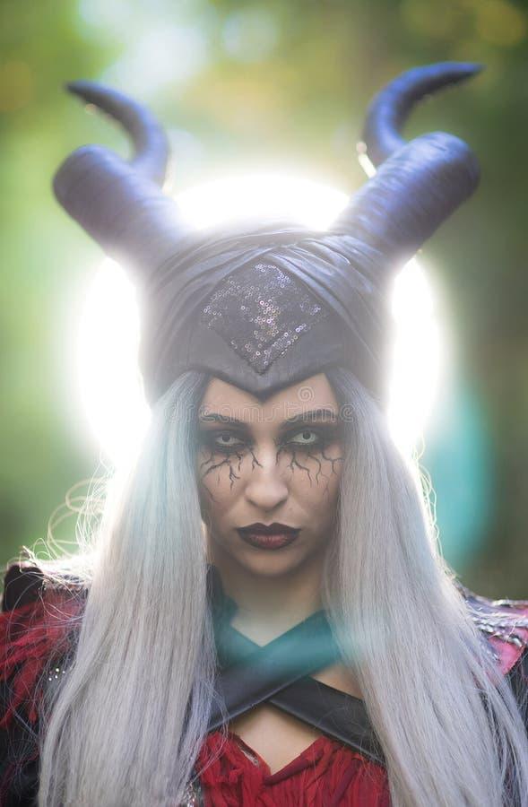 Mulher terrível com composição surpreendente do cabelo preto da prata de chifres com luz branca no fundo foto de stock royalty free