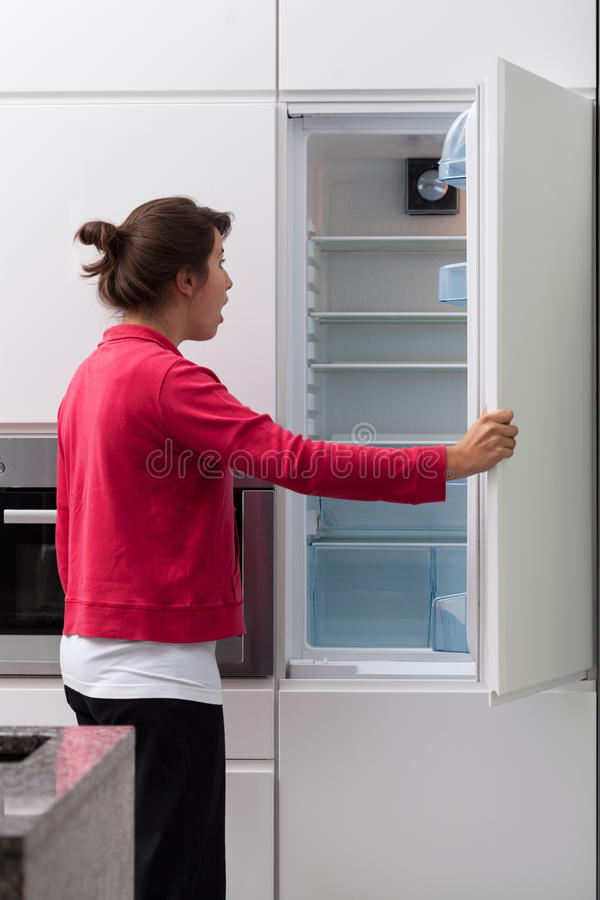 Mulher terrificada contra o refrigerador vazio fotos de stock royalty free