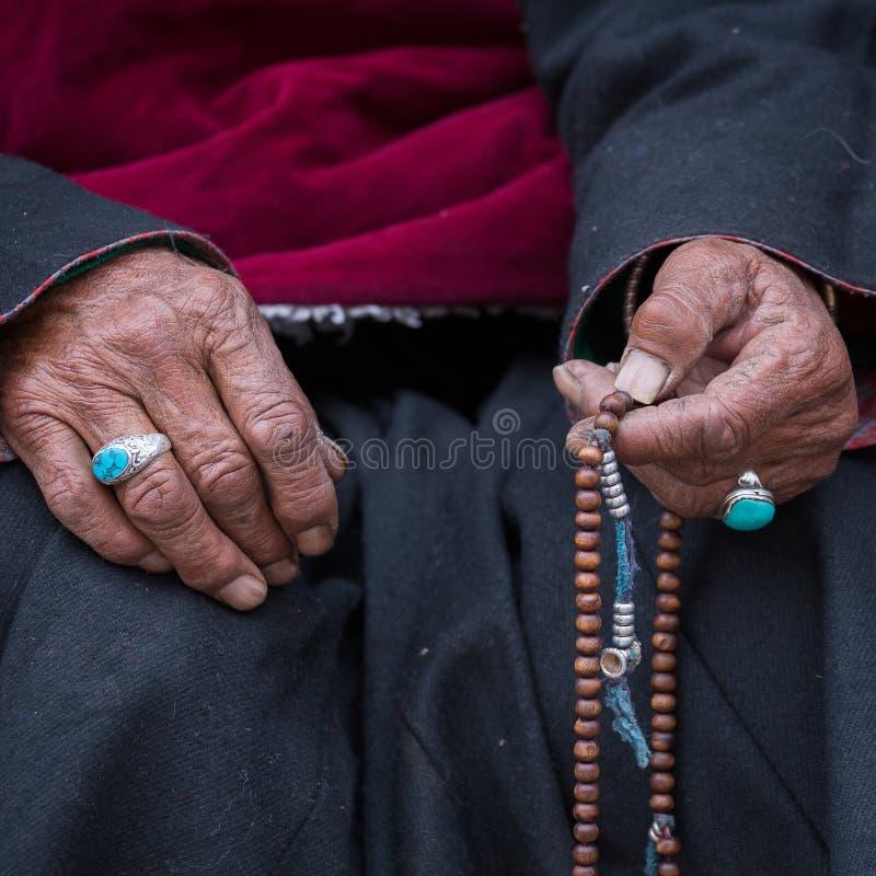 Mulher tibetana idosa que guarda o rosário budista, Ladakh, Índia Mão e rosário imagens de stock royalty free