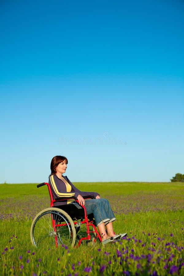 Mulher tida desvantagens na cadeira de rodas foto de stock