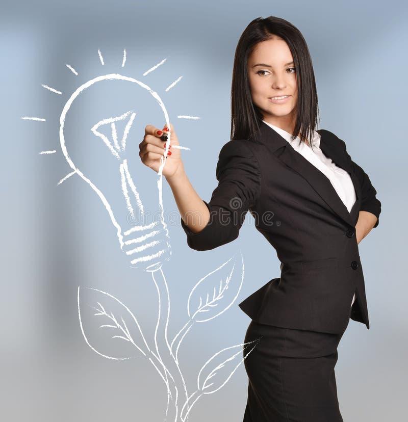 A mulher tira a árvore da luz de bulbo que está no sumário fotos de stock royalty free