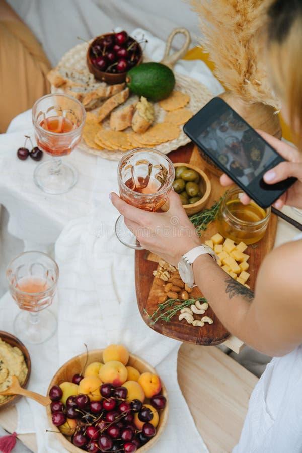 Mulher tirando uma foto do copo de vinho em mãos sobre uma mesa com vários aperitivos fotografia de stock
