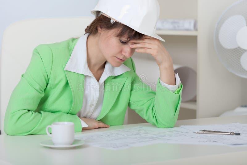 Mulher Tired - o coordenador no capacete senta-se no escritório foto de stock royalty free