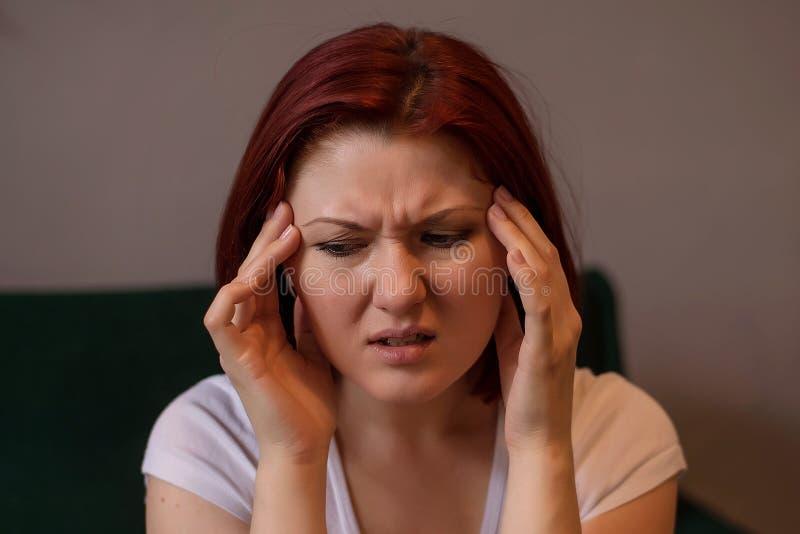 Mulher tocante ou que faz massagens templos com a careta infeliz da cara Conceito da enxaqueca, a mental ou a física da saúde da  imagem de stock