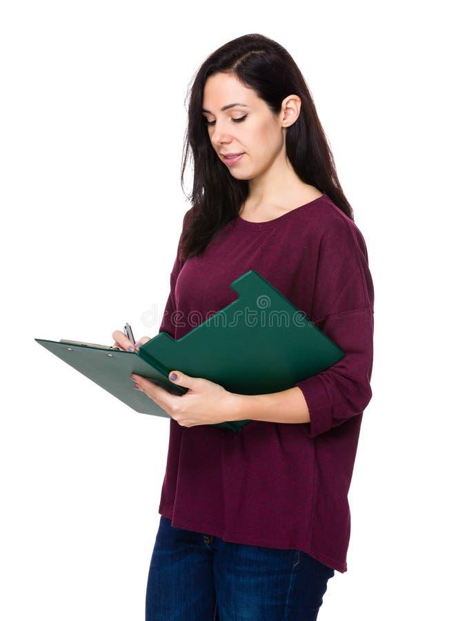 A mulher toma a nota na prancheta fotografia de stock royalty free