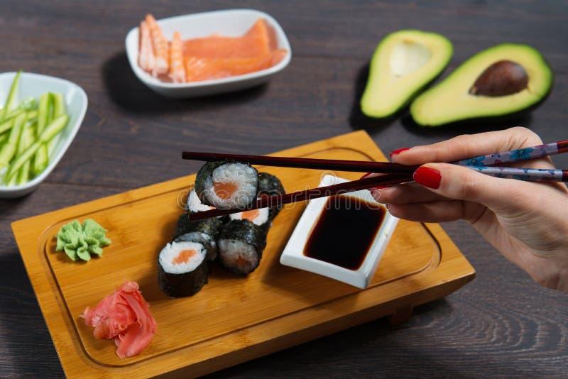 A mulher toma os rolos de sushi usando hashis imagens de stock royalty free