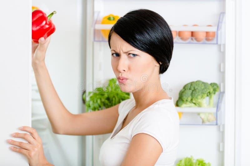 A mulher toma a pimenta de sino do refrigerador aberto fotos de stock