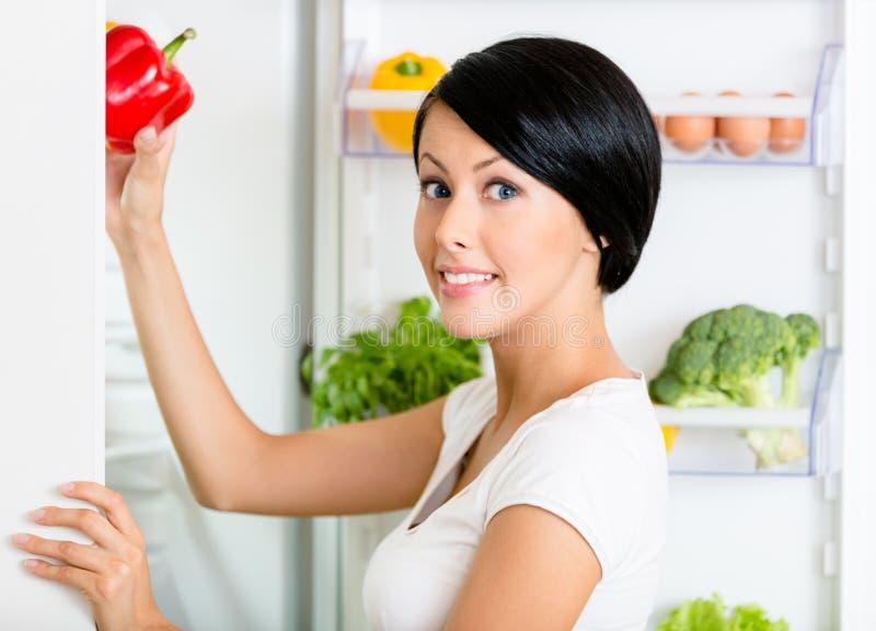 A mulher toma a pimenta doce do refrigerador aberto imagens de stock