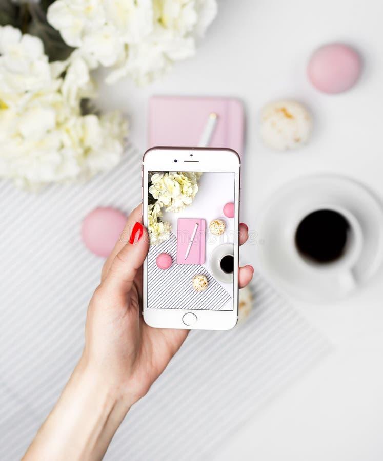 A mulher toma uma imagem do espa?o de trabalho em um smartphone Caderno, pena, bolinhos de am?ndoa, caf? e flores cor-de-rosa no  fotos de stock royalty free