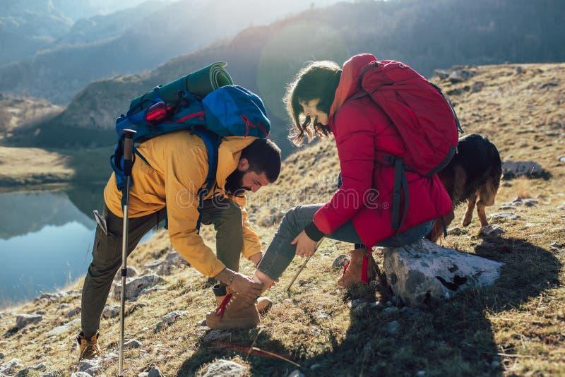 A mulher torceu seu tornozelo ao caminhar, seu amigo usa o kit de primeiros socorros para tender ao ferimento fotografia de stock
