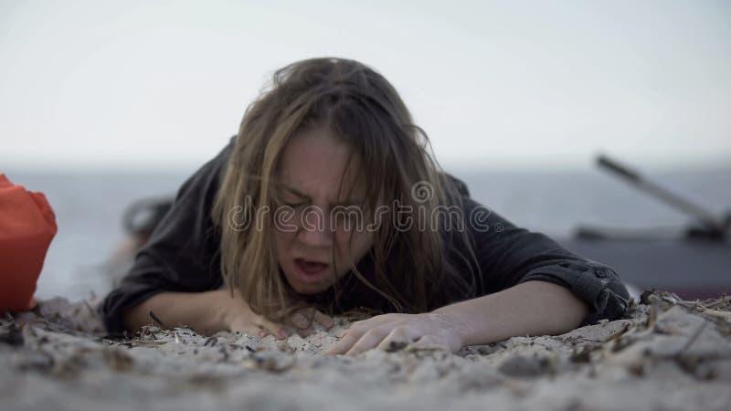 Mulher tossindo, tentando rastejar na areia, sobrevivendo à catástrofe natural, vítima fotos de stock royalty free