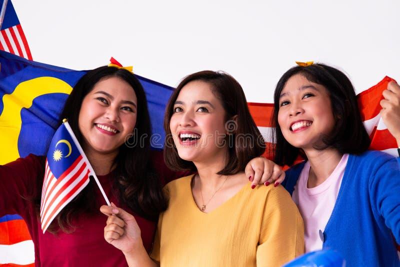 Mulher três malay que guarda a bandeira nacional malaia foto de stock royalty free