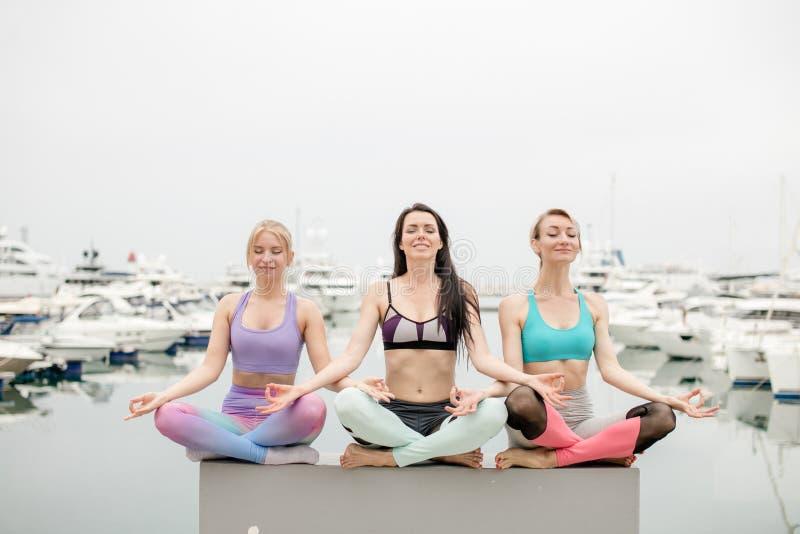 A mulher três tem a meditação na classe da ioga, exterior no cais marinho imagem de stock