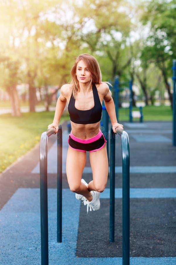 Mulher tração-UPS ela mesma em barras horizontais na terra de esportes no parque foto de stock