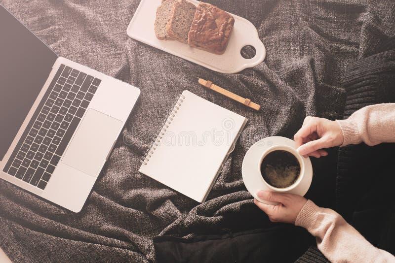 Mulher trabalha em casa para ficar em casa por ordem de pandemia de coronavírus trabalho online e aprendizagem em cama com o lapt imagem de stock