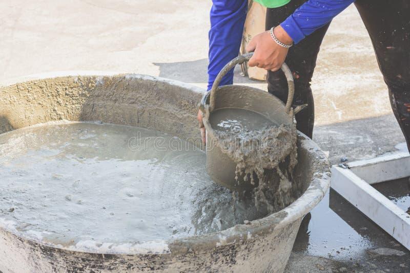Mulher trabalhadora mistura cimento em balde foto de stock