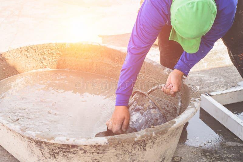 Mulher trabalhadora mistura cimento em balde imagens de stock