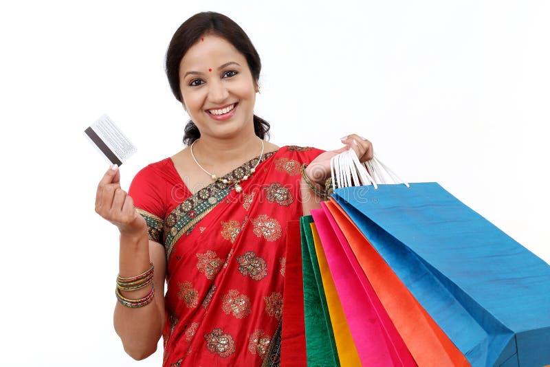 Mulher tradicional de sorriso dos jovens com sacos de compras imagem de stock
