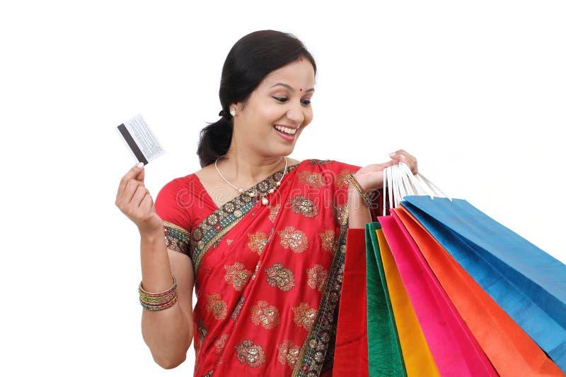 Mulher tradicional de sorriso dos jovens com sacos de compras imagem de stock royalty free