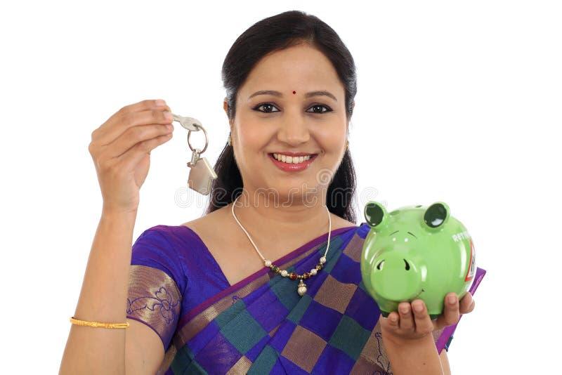 Mulher tradicional de sorriso que guarda a chave do mealheiro e da casa fotografia de stock