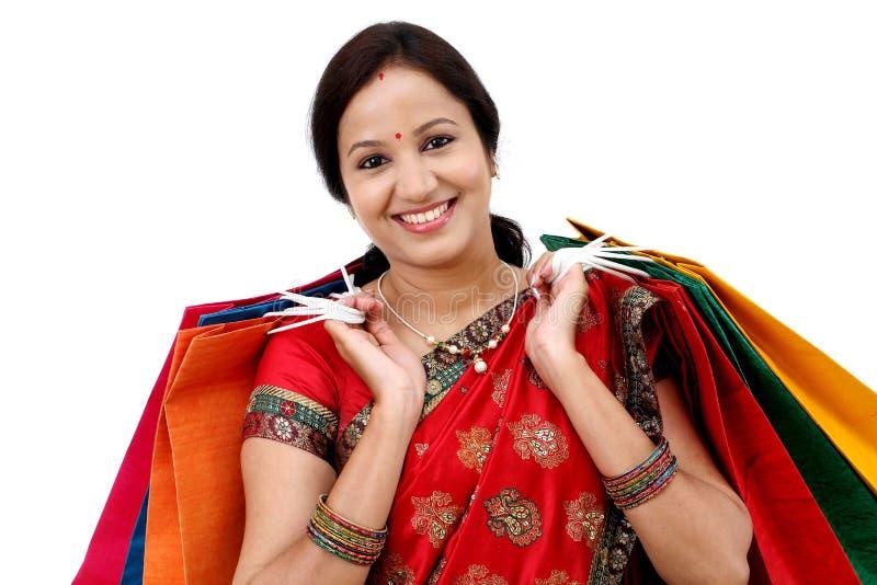 Mulher tradicional nova de sorriso com sacos de compras fotografia de stock royalty free