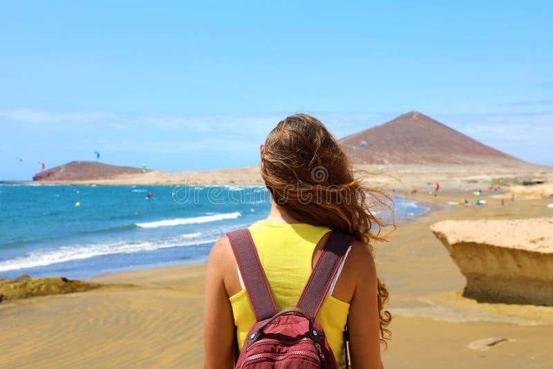 A mulher traseira da vista que aprecia surfistas do papagaio mostra na praia do EL Medano, Tenerife, Ilhas Canárias fotos de stock