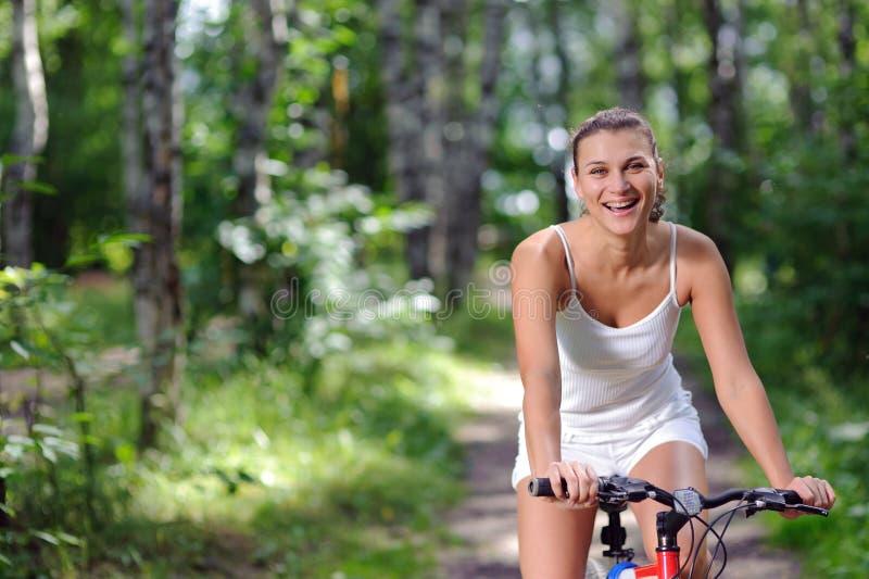 Mulher triguenha ativa na bicicleta vermelha fotografia de stock royalty free