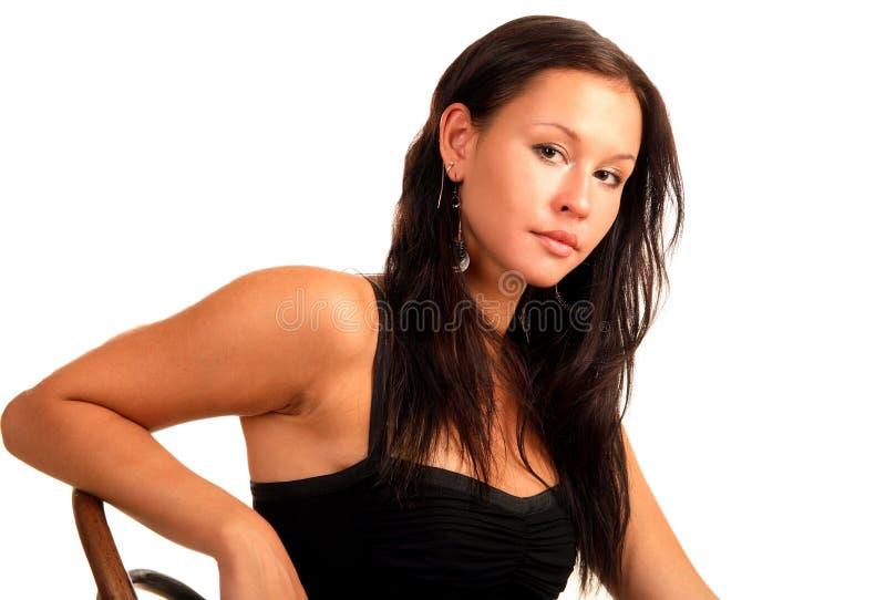 A mulher triguenha atrativa senta-se na cadeira imagem de stock