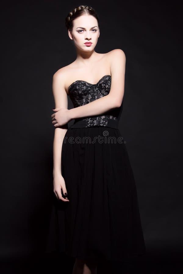 Mulher triguenha bonita no vestido preto elegante. foto de stock royalty free
