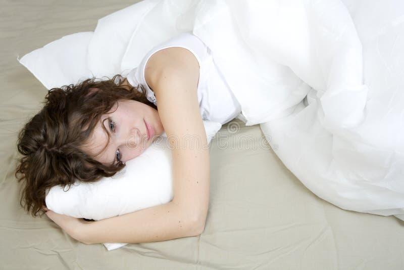 Mulher triguenha da onda que encontra-se na cama fotografia de stock royalty free