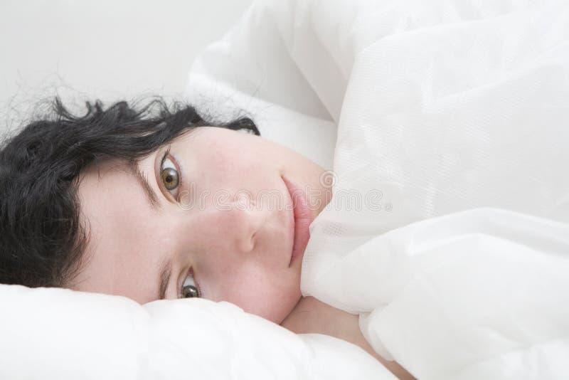 Mulher triguenha da onda que encontra-se na cama foto de stock royalty free