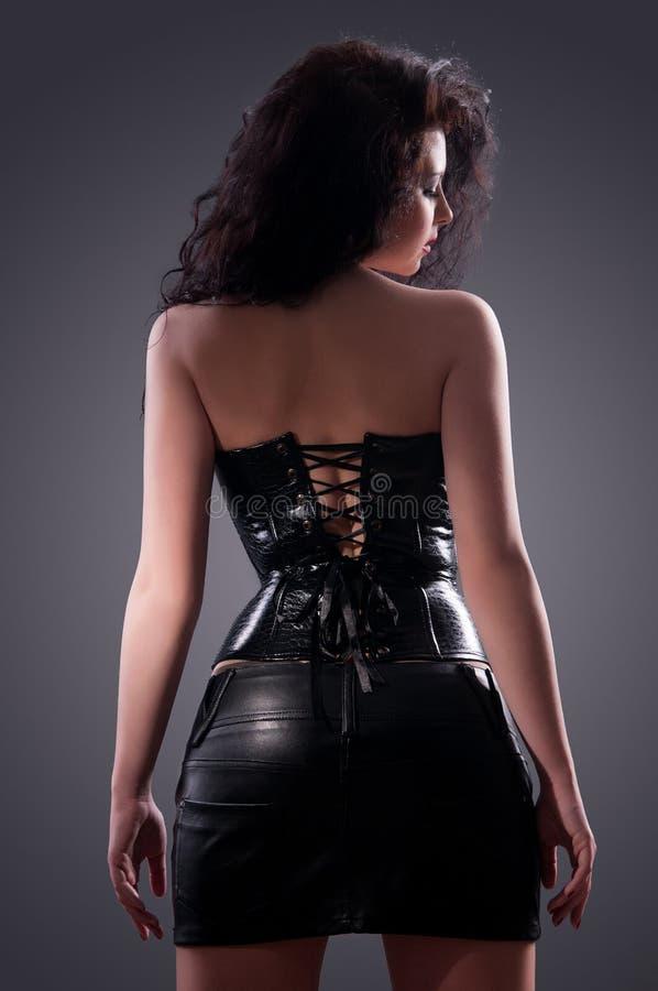 Mulher triguenha desejada que levanta no espartilho de couro imagens de stock