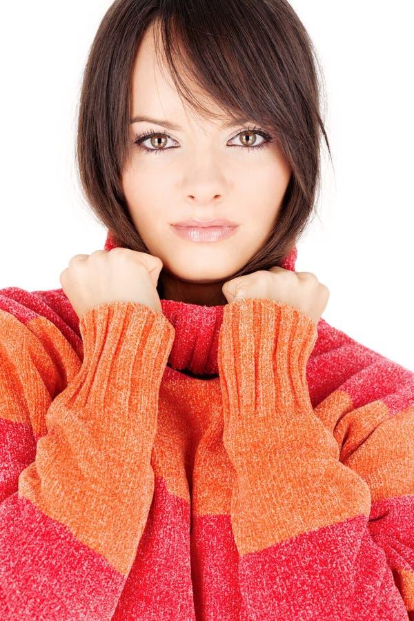 Mulher triguenha em uma camisola vermelho-alaranjada de lãs imagem de stock