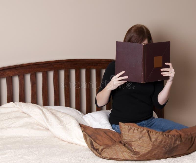 A mulher triguenha lê dentro a cama imagens de stock