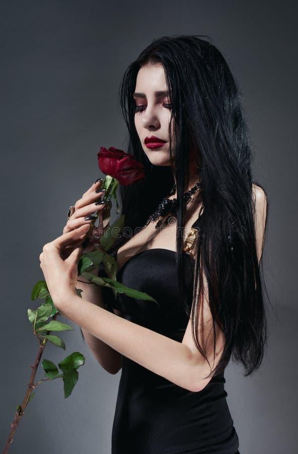 A mulher triguenha no vestido preto com vermelho levantou-se foto de stock