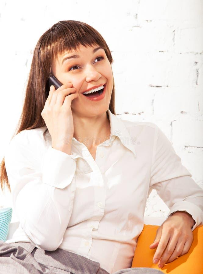 A mulher triguenha nova fala no telefone de pilha fotos de stock royalty free