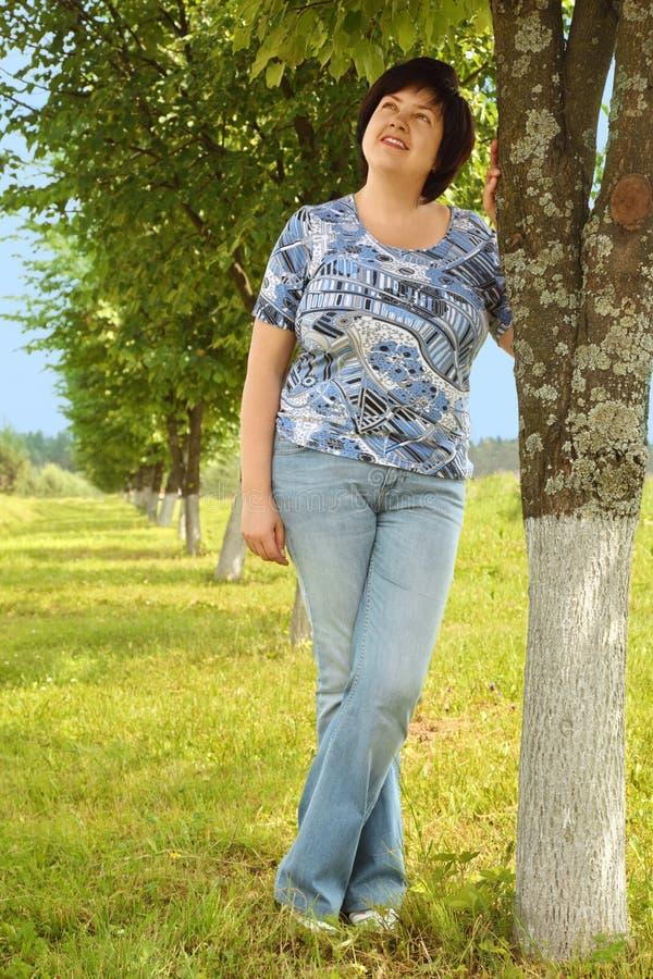 Mulher triguenha Plumpy que está no gramado perto da árvore imagens de stock