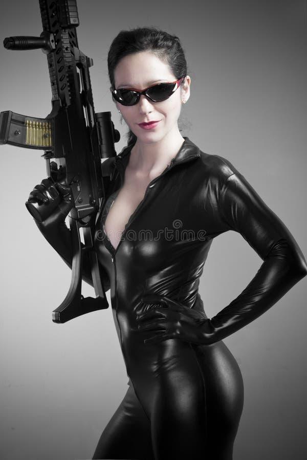 Mulher triguenha 'sexy' no jumpsuit do látex com arma pesada fotografia de stock royalty free