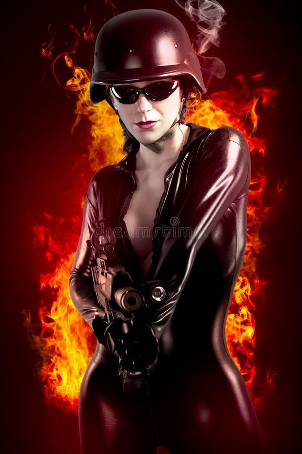 Mulher triguenha 'sexy' no jumpsuit do látex com arma pesada e capacete ilustração stock