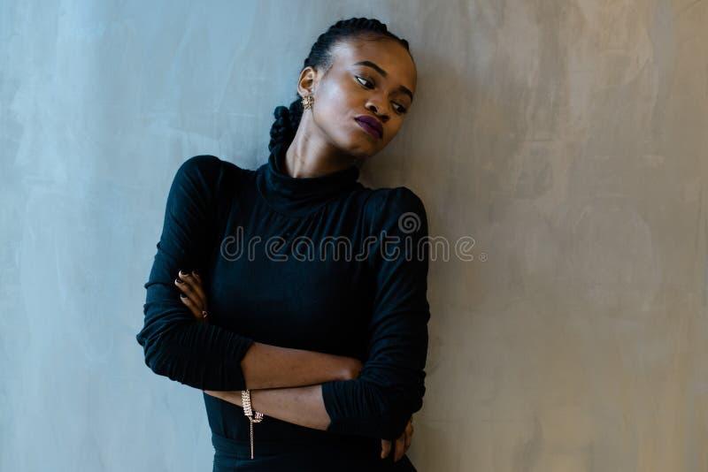 A mulher triste afro-americano vestiu-se no preto inclinado contra a parede fotografia de stock royalty free