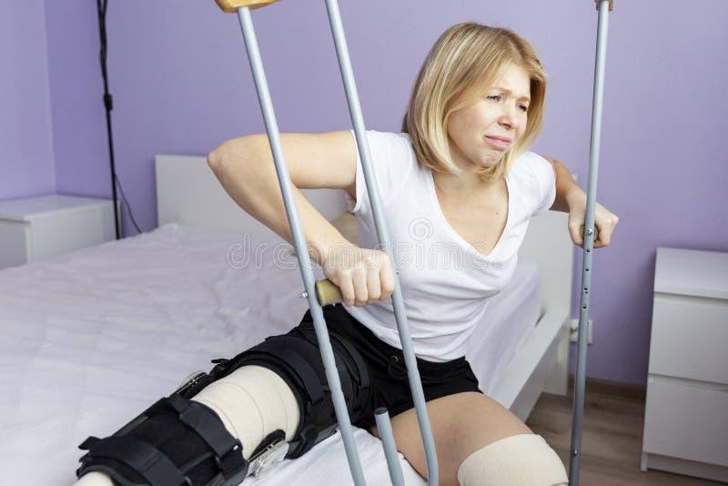 A mulher triste após uma operação em seu pé está sentando-se na cama fotografia de stock royalty free