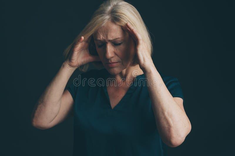 Mulher triste com dor de cabeça se sentindo mal fotografia de stock