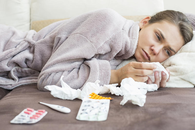 Mulher triste com tecido e medicinas que encontram-se na cama foto de stock