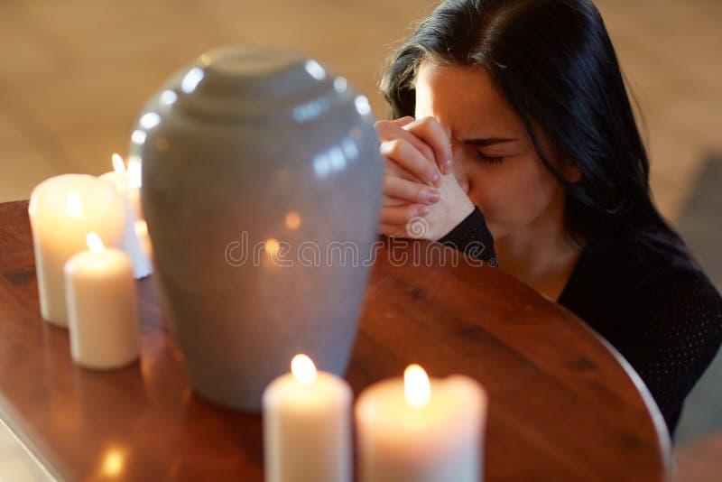 Mulher triste com urna funerária que reza na igreja foto de stock