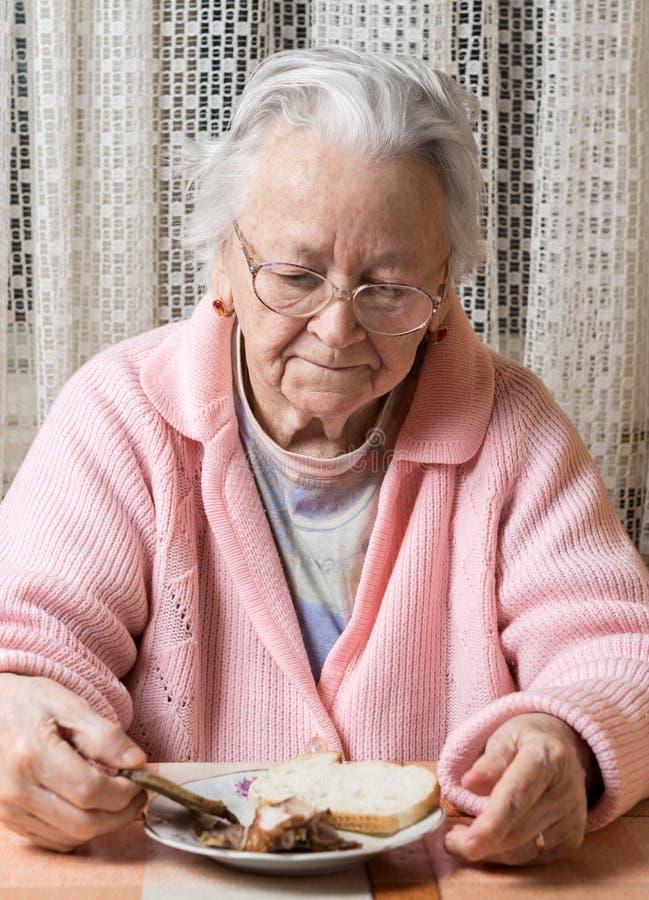 Mulher triste idosa que come em casa fotografia de stock royalty free
