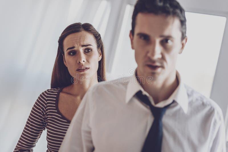 Mulher triste infeliz que olha seu marido imagem de stock
