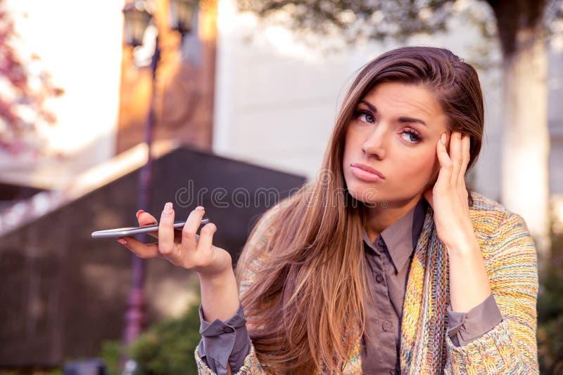 Mulher triste irritada com parte externa ereta do telefone celular na rua com um fundo urbano fotografia de stock