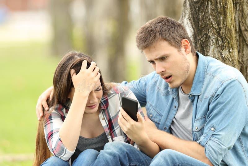 A mulher triste mostra a mensagem a um amigo surpreendido fotografia de stock royalty free