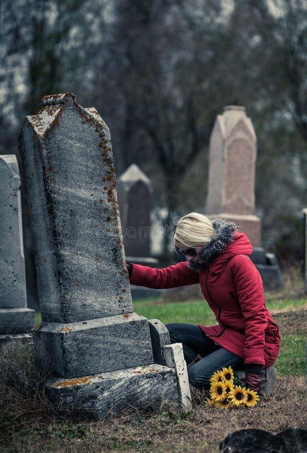 Mulher triste no de toque de lamentação amado sua lápide imagens de stock