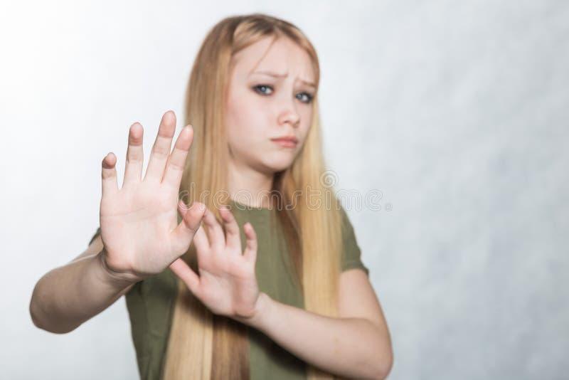 Mulher triste nova que aumenta as palmas no nenhum ou no gesto da parada, querendo diminuir a oferta fotografia de stock